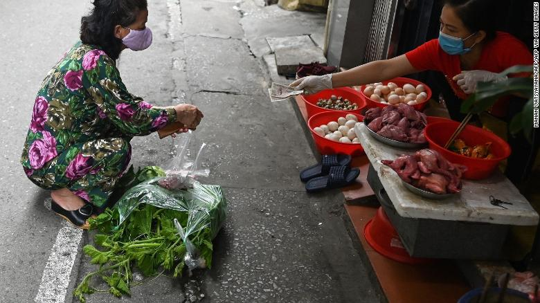 A woman practises social distancing while shopping for groceries from behind a line at a wet market in Hanoi.